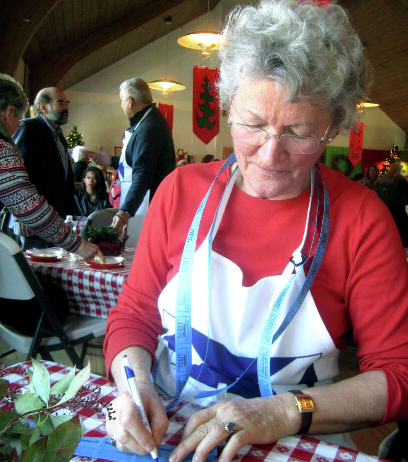 Sabine Gibson, chairwoman of St. Andrew's Episcopal Church's Nov. 23, 2013 Christmas bazaar, keeps busy during the event handling raffle ticket sales. Photo: Norm Cummings / The News-Times