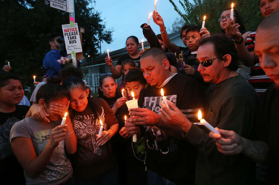 Leo Hernandez (center) and his father, Ruben Hernandez (right) gather with relatives and friends at a Dec. 4 vigil for his daughter, 17-year-old Megan Hernandez, on Mission Road. The young mother was stabbed to death a day earlier. Photo: Jerry Lara / San Antonio Express-News