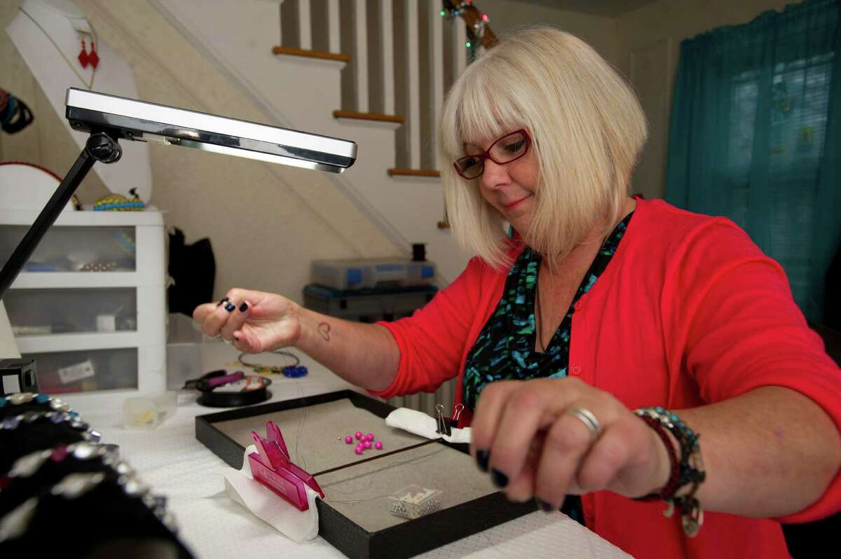Sandy D'Andrea makes jewelry for Jewels for Hope, the company she owns with her daughter, Stevie, on Friday, December 6, 2013.