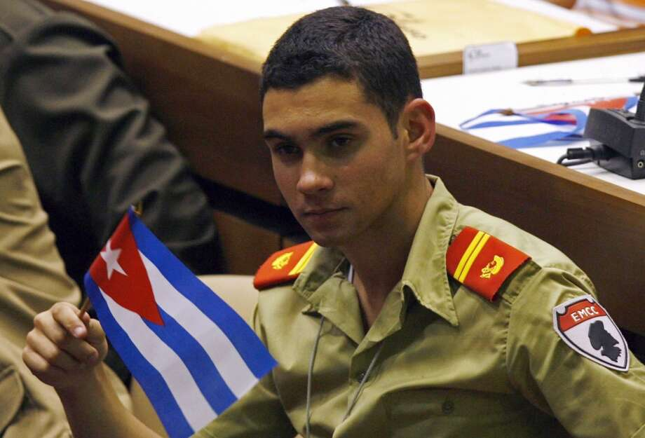 Elian GonzaleZ holds a Cuban flag during the UJC, Union of Young Communists, congress in Havana Sunday April 4, 2010. Gonzalez, the Cuban boy at the center of an international custody battle 10 years ago in April 2000, attended Cuba's Young Communist Union wearing an olive green military school uniform.(AP Photo/Ismael Francisco, Prensa Latina) Photo: AP