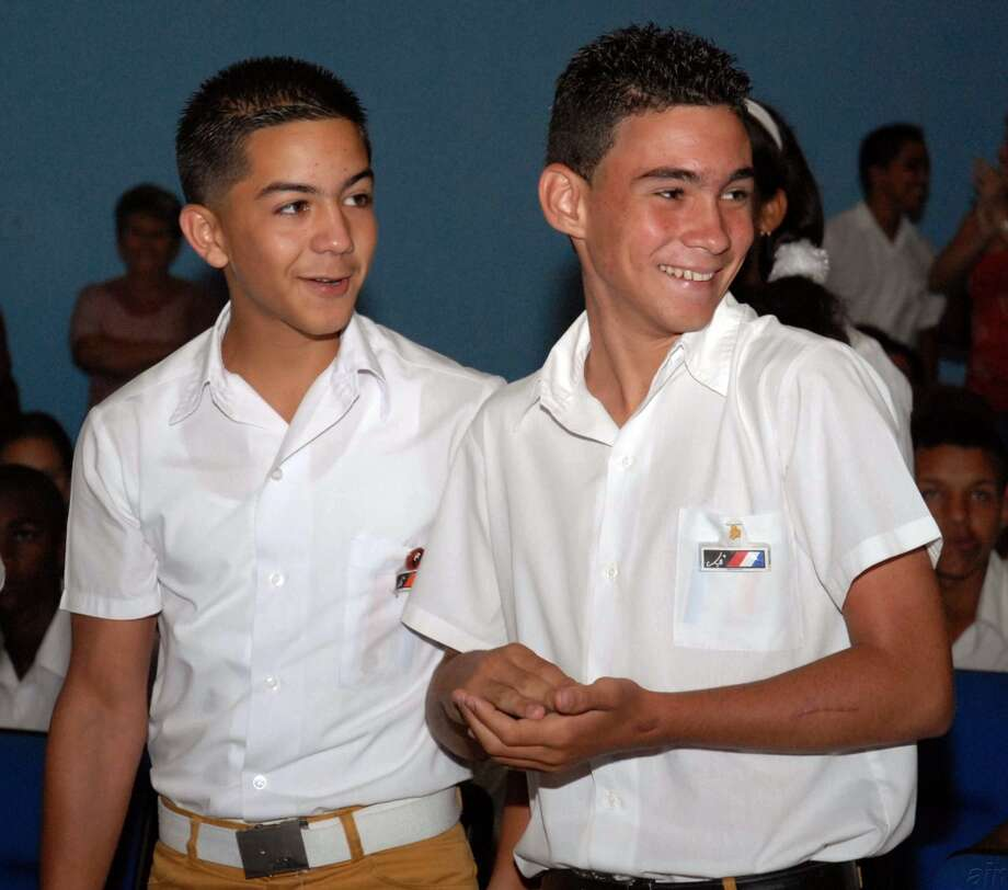 "Cuban young militant Elian Gonzalez, right, accompanied by a fellow militant, smiles as he attends an event marking the 80th anniversary of the birth of the Cuban National hero, Argentinean Ernesto ""Che"" Guevara in Havana, Saturday, June 14, 2008. Gonzalez, the Cuban boy at the center of an international custody battle eight years ago, has joined Cuba's Young Communist Union. Communist youth newspaper Juventud Rebelde quotes Elian Gonzalez as saying he will never let down ex-President Fidel Castro and his brother Raul Castro, who succeeded Fidel earlier this year. (AP Photo/AIN, Marisol Ruiz Zoto) Photo: AP"