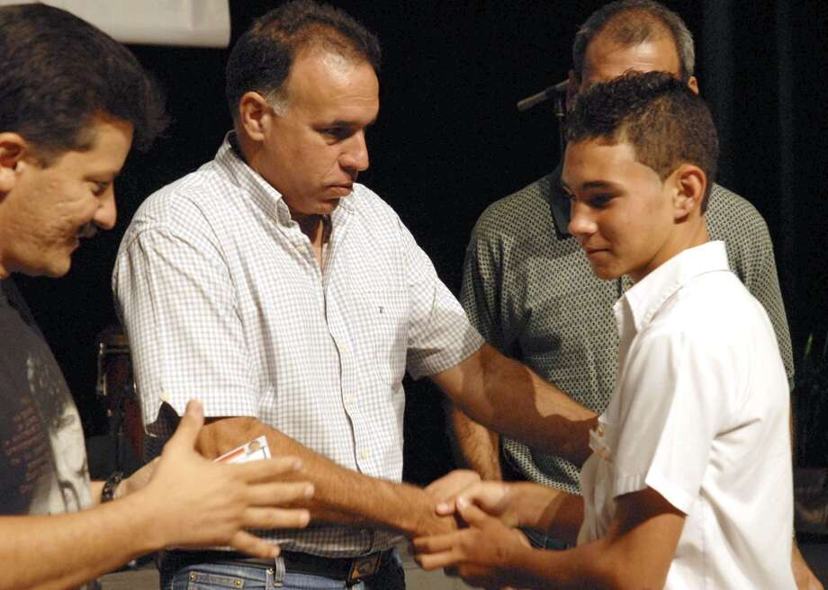 "Julio Martinez, left, first secretary of the Union of Communist Young people of Cuba, UJC, gives an UJC's identity card to Cuban young Elian Gonzalez, left, during an event marking the 80th anniversary of the birth of the Cuban National hero, Argentinean Ernesto ""Che"" Guevara in Havana, Saturday, June 14, 2008. Gonzalez, the Cuban boy at the center of an international custody battle eight years ago, has joined Cuba's Young Communist Union. Communist youth newspaper Juventud Rebelde quotes Elian Gonzalez as saying he will never let down ex-President Fidel Castro and his brother Raul Castro, who succeeded Fidel earlier this year. (AP Photo/AIN) Photo: AP"