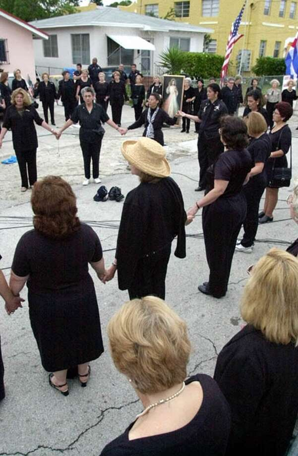 Members of Mothers Against Repression pray the rosary as they stand hand in hand, Saturday, April 15, 2000, outside the home of the Miami relatives of Elian Gonzalez. The tug-of-war over Gonzalez is turning into wait, with two federal courts considering the boys fate and protesters in Little Havana maintaining an uneasy vigil. (AP Photo/Amy E. Conn) Photo: AP