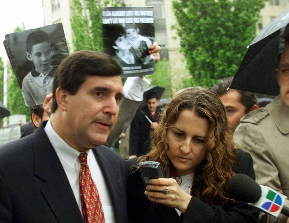 As supporters in favor of keeping Elian Gonzalez in the United States hold up pictures of the six-year-old, Miami Mayor Joe Corollo talks with a reporter as he leaves a sidewalk news conference outside the Cuban Interest Section Tuesday, April 18, 2000 in Washington.   (AP Photo/Ted S. Warren)   Cuban Interest Section Photo: AP