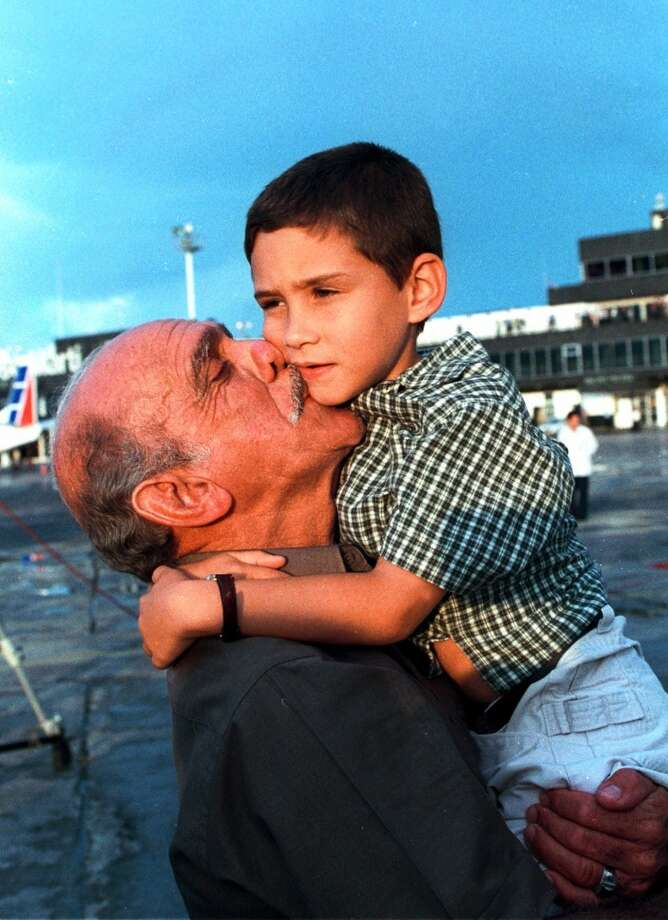 Elian Gonzalez is welcomed by his grandfather Rolando Betancourt Wednesday June 28, 2000 upon his arrival at the Jose Marti Airport in Havana, Cuba.  Seven months after he was cast adrift in the Florida straits, Elian Gonzalez returned to his native Cuba, bringing to a close an international custody battle laced with Cold War passions. (AP Photo/Granma,Pool) Photo: AP
