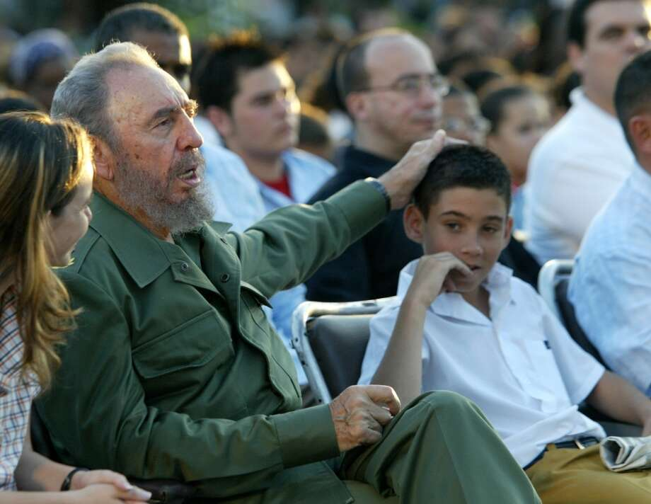 Cuban President Fidel Castro, puts his hand on the head of Elian Gonzalez Tuesday, Dec. 6, 2005 in the coastal city of Cardenas Cuba. Gonzalez. Gonzalez, wearing his school uniform, sat next to Castro at the political event recalling the island's successful campaign to gain custody of the boy from the United States. The Cuban boy thrust into the center of an international custody battle six years ago, celebrated his 12th birthday Tuesday listening to a two-hour speech by Castro. (AP Photo/Jorge Rey) Photo: AP