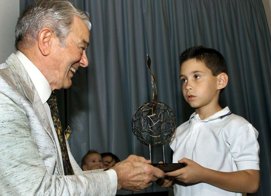 """Cuban shipwreck survivor Elian Gonzalez receives the Free Spirit Award from Al Neuharth, founder of USA Today and the Freedom Forum, Friday Feb. 8, 2002 in Havana, Cuba. The private ceremony was attended by Elian's family and a few Cuban officials. (AP Photo/Jose Goitia)   HOUCHRON CAPTION  (02/09/2002):  Shipwreck survivor Elian Gonzalez, now 8, receives the Freedom Forum's Free Spirit Award from Al Neuharth, founder of USA Today and the Freedom Forum, in Havana on Friday. Throughout his ordeal """"Elian was able to come back and laugh no matter how many grown-ups were tugging at him,"""" Neuharth said. Photo: AP"""