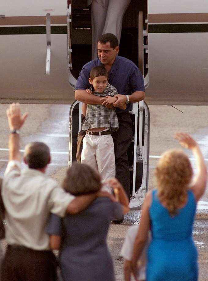 Relatives welcome Elian Gonzalez as he arrives to Havana's Jose Marti international airport carried by his father Juan Miguel Gonzalez, Wednesday, June 28, 2000.   (AP Photo/Ricardo Mazalan)  HOUCHRON CAPTION (06/29/2000):  Elian Gonzalez and his father, Juan Miguel,  arrive at the Havana airport Wednesday to an enthusiastic but restrained reception, which was requested by Cuban government leaders. Photo: AP