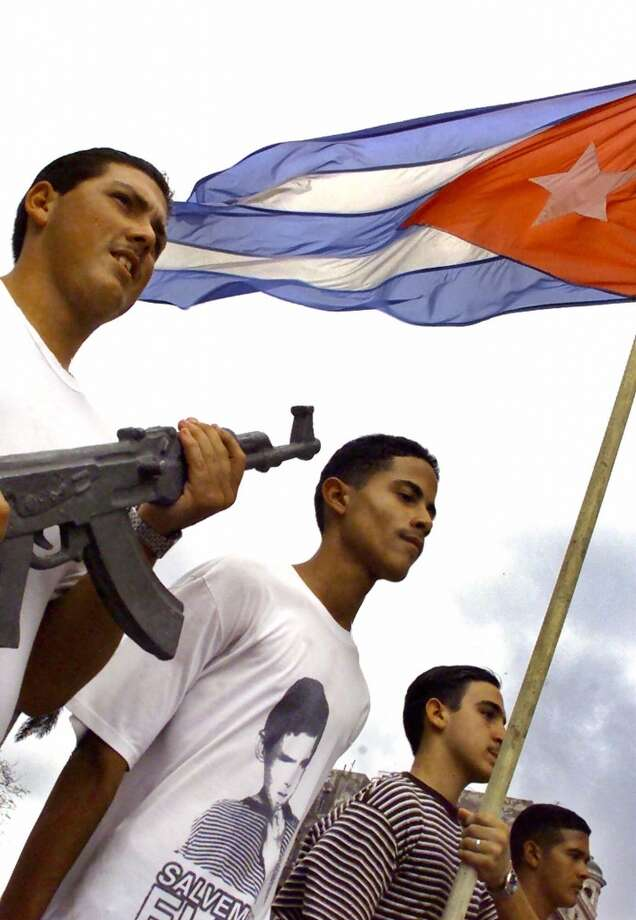 "Cuban high school students, one of which is wearing a 'Save Elian' T-shirt, participate in a school military excercise in Havana on Thursday, April 13, 2000. Cubans are waiting to see when and if Elian will return to Cuba with his father. (AP Photo/Scott Dalton)  HOUCHRON CAPTION (04/14/2000):  Cuban students, one wearing a ""Save Elian"" T-shirt, take part in a school military exercise Thursday in Havana. The Elian Gonzalez saga is closely followed in Cuba. Photo: AP"