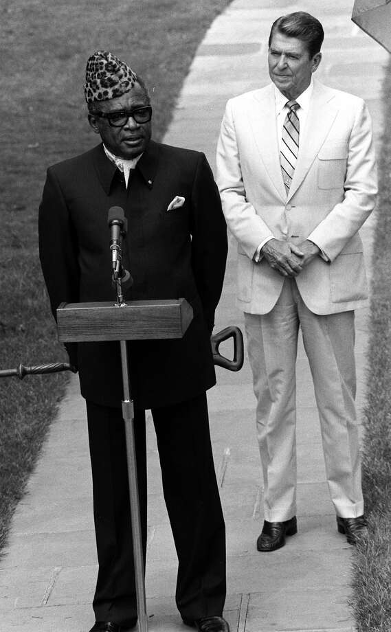 "President Ronald Reagan stands behind President Mobutu Sese Seko of Zaire during a White House news conference in Washington in this  August 5,  1983 file photo. Reagan thanked the visiting leader for his  ""courageous action"" in sending troops to help Chad resist a  Libyan-backed revolt. Mobutu is remembered for his history of corruption and human rights violations."