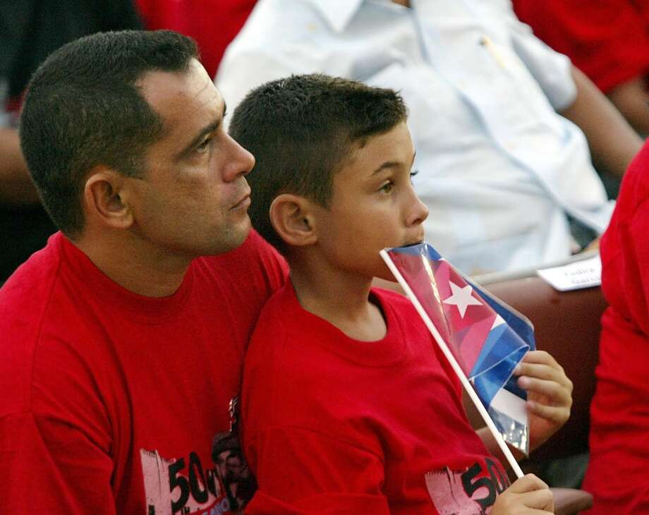 Cuban  balsero  boy Elian Gonzalez sits on the lap of his father Jose Miguel as they attend the celebration of the 50th anniversary of the Moncada barracks attack, 26 July, 2003 in Santiago de Cuba. The failed attempt to seize the Cuban Army post in 1953 by Fidel Castro and his companions marks the beginning of the Cuban Revolution.   AFP PHOTO/Adalberto ROQUE   (Photo credit should read ADALBERTO ROQUE/AFP/Getty Images) Photo: AFP/Getty Images