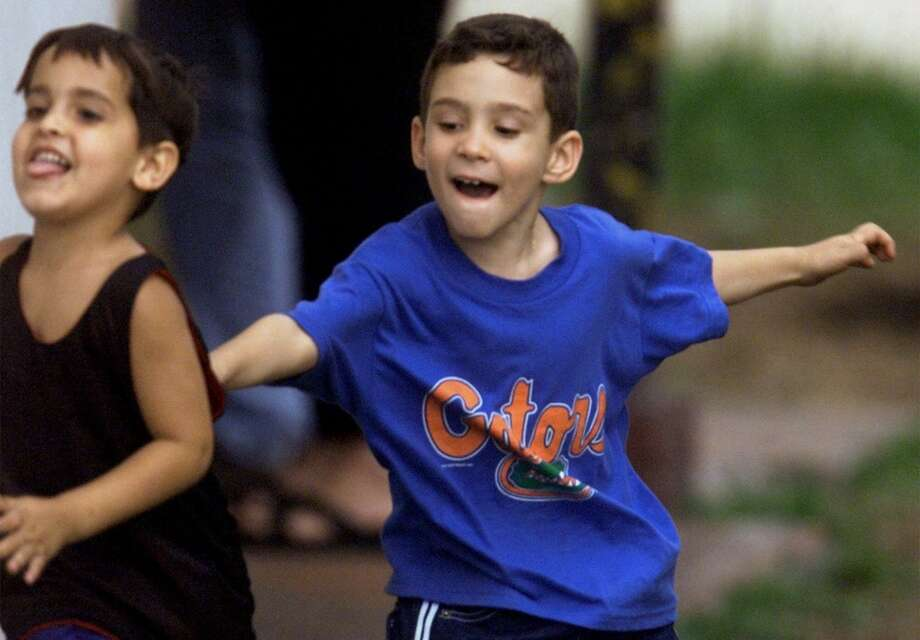 Elian Gonzalez, right, plays tag with his cousin Lazarito Gonzalez in the backyard of their relative's home Sunday April 16, 2000 in the Little Havana district of Miami.(AP Photo/Beth A. Keiser) Photo: AP