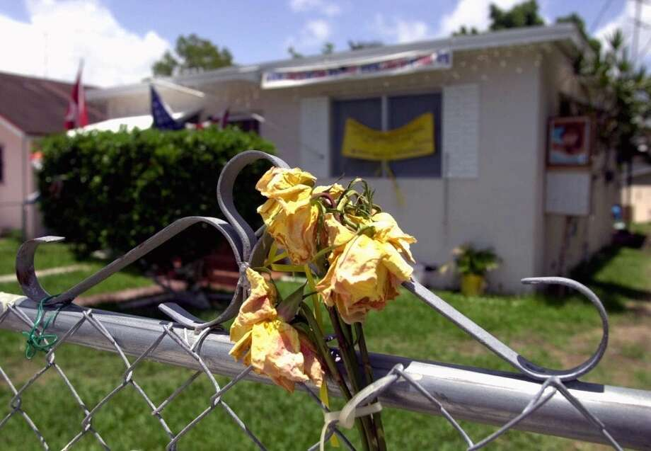 Wilted flowers sit in the hot Florida sun at the former home of Elian Gonzalez's Miami family Thursday, June 29, 2000, the day after the 6-year-old boy returned to Cuba. (AP Photo/Amy E. Conn)  HOUCHRON CAPTION (06/30/2000): Wilted flowers sit on a fence at the former home of Elian Gonzalez's Miami relatives, who moved after the boy was taken from them. Photo: AP