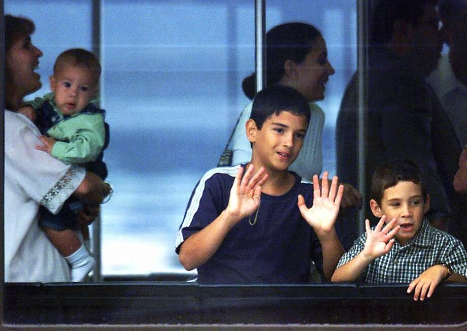 Elian Gonzalez waves from a mobile lounge set up as a makeshift immigration office at Dulles International Airport on Wednesday, June 28, 2000. Elian's step-mother Nersy, left, is holding Elian's step-brother Hianny. Others are not identified. (AP Photo/Hyungwon Kang) Photo: AP