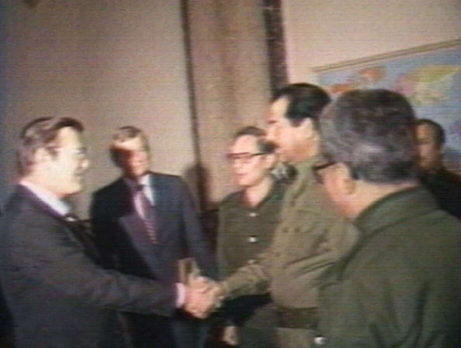 U.S. Secretary of Defense Donald Rumsfeld (L) and Iraqi president Saddam Hussein shake hands December 20, 1983 in Baghdad, Iraq.  Rumsfeld met with Hussein during the war between Iran and Iraq as an  envoy for former U.S. President Ronald Reagan. In 2003, the U.S. invaded Iraq and deposed Hussein after accusing the nation of possessing weapons of mass destruction. Hussein was later executed by the new Iraqi government. / 2002 Getty Images