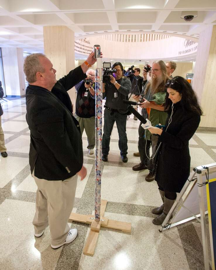 Chaz Stevens from Deerfield Beach, Florida assembles his Festivus pole out of beer cans in the rotunda of the Florida Capitol as the media looks on December 11, 2013 in Tallahassee, Florida.  Stevens display was intended to counter the religious Christian Nativity manger on display. Based on an episode of the television sitcom Seinfeld, Festivus has become a secular holiday celebrated on December 23 to represent the antithesis of the commercialism of the Christmas season. (Photo by Mark Wallheiser/Getty Images) Photo: Mark Wallheiser, Getty Images