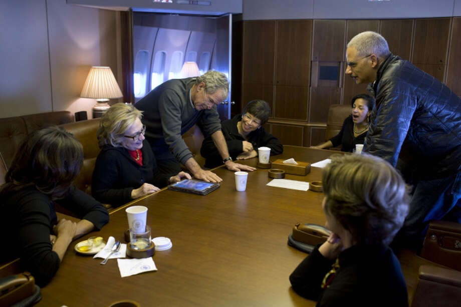 Aboard Air Force One, former President Bush shows photos of his paintings to, from left, First Lady Michelle Obama, former Secretary of State Hillary Clinton, Valerie Jarrett, National Security Advisor Susan E. Rice, Attorney General Eric Holder and former First Lady Laura Bush, Dec. 9, 2013. (Official White House Photo by Pete Souza)