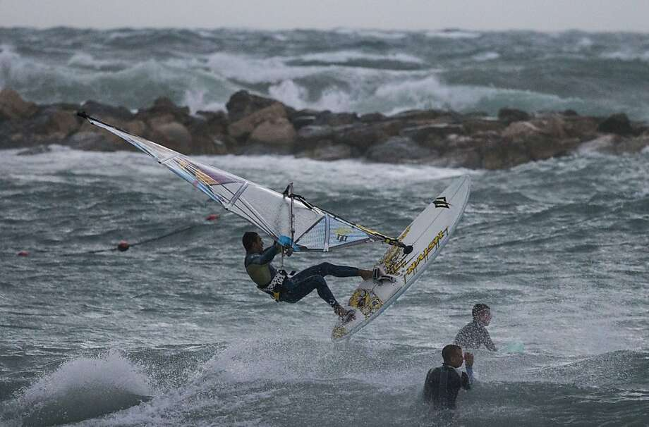A sailboard skips over swellsin rough seas off Tel Aviv as a winter weather front plows into Israel, bringing rain, snow and freezing temperatures. Photo: Jack Guez, AFP/Getty Images