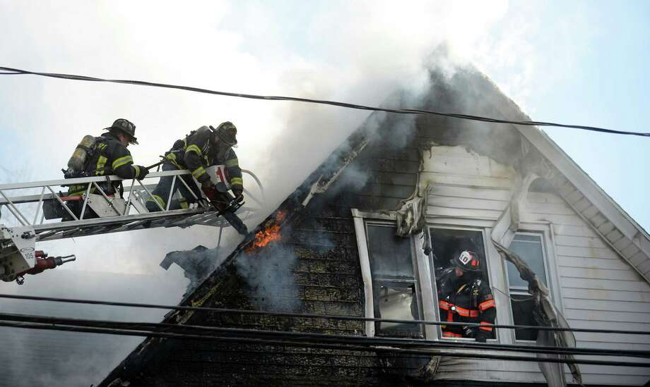 Firefighters work to extinguish a fire on the second floor of a house on Capitol Avenue in Bridgeport, Conn. Wednesday, Dec. 11, 2013. Photo: Autumn Driscoll / Connecticut Post