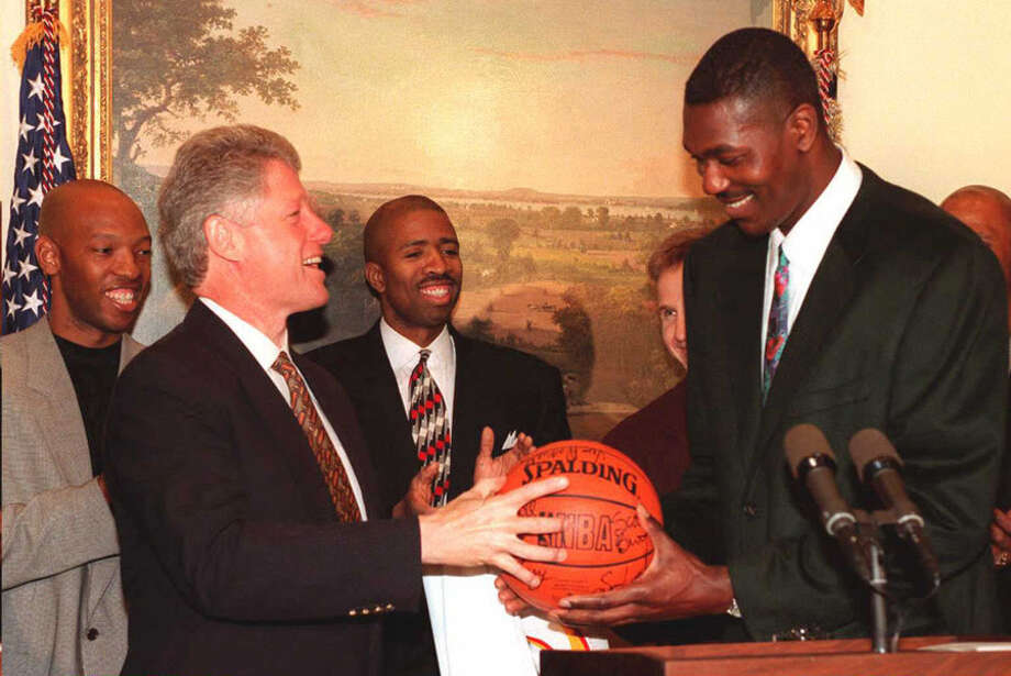 President Bill Clinton (L) accepts a basketball from Houston Rockets' Hakeem Olajuwon at the White House in Washington following the Rockets' 1994 NBA Championship.  Houston Rockets' Sam Cassell, (L) Kenny Smith (C) and Sam Brooks stand behind President Clinton and Olajuwon. Photo: ROBERT GIROUX, AFP/Getty Images / AFP