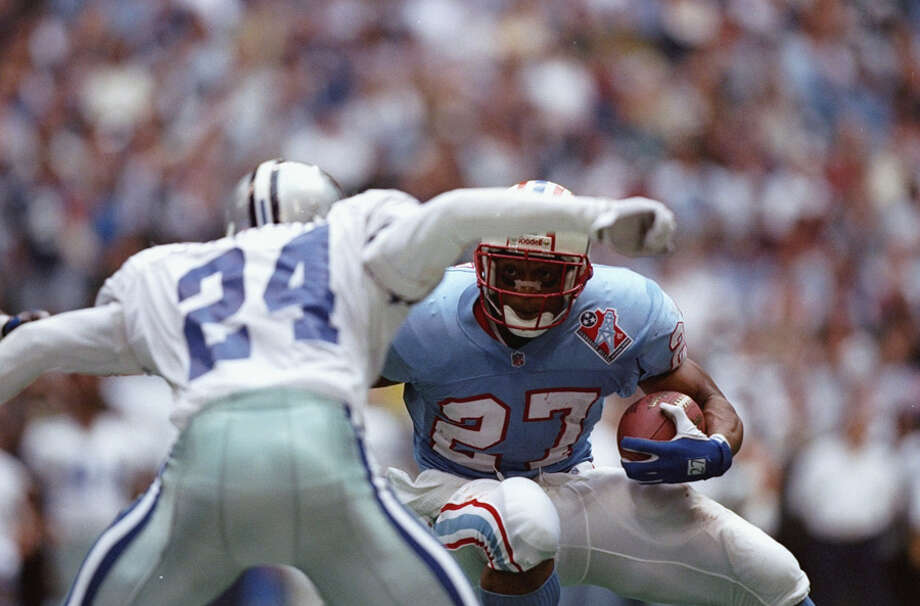 Running back Eddie George of the Houston Oilers (right) tries to run with the ball past defensive back Omar Stoutmire of the Dallas Cowboys during a game at Texas Stadium in Irving.  The Oilers won the game 27-14.  Photo: Stephen Dunn, Getty Images / Getty Images North America