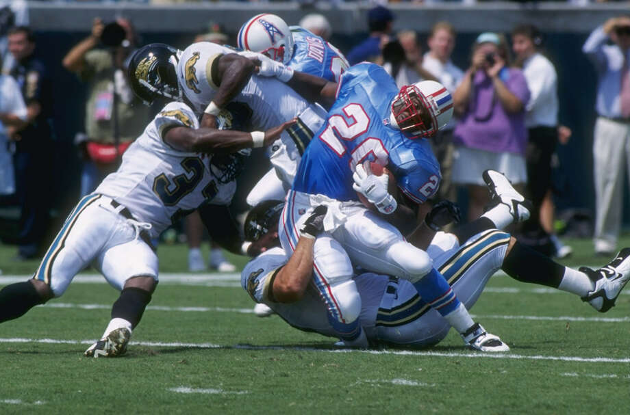 Running back Rodney Thomas #20 of the Houston Oilers is hit and wrapped up by linebacker Travis Davis #45 of the Jacksonville Jaguars during a carry in the Oilers 34-27 victory over the Jaguars at Jacksonville Municiple Stadium in Jacksonville. Photo: Zoran Milich, Getty Images / Getty Images North America