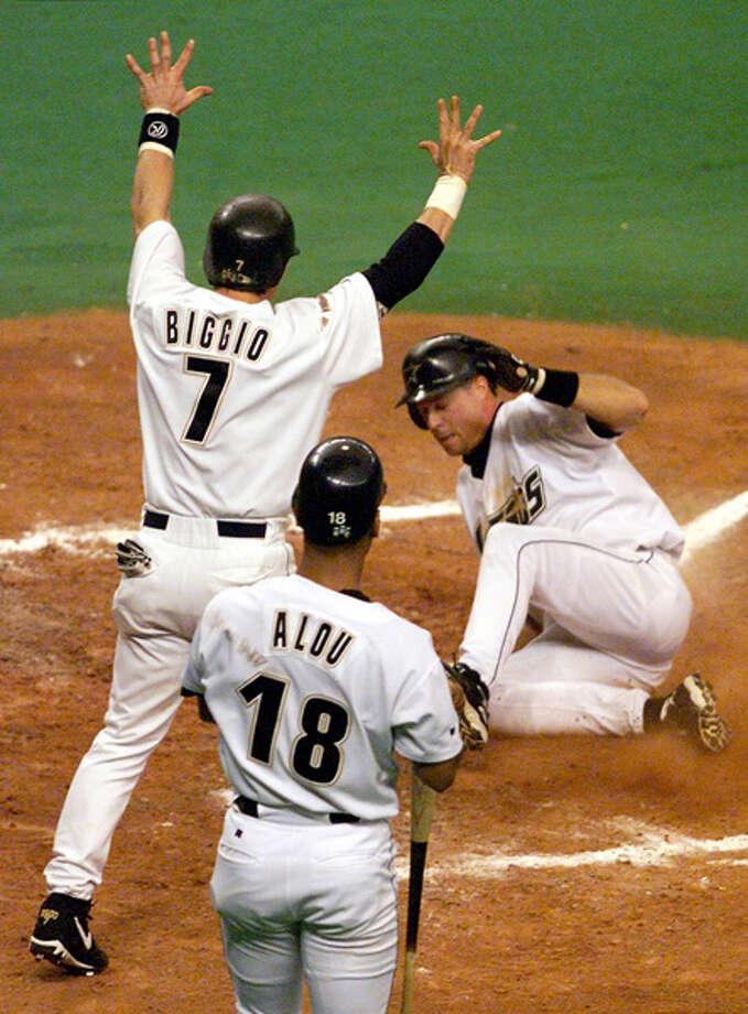 Bill Spiers (R) of the Houston Astros slides in safely to score a run as teammates Craig Biggio (7) and Moises Alou (18) look on October 1, 1998 during the first inning of game two in the Division Series with the San Diego Padres in the Houston Astrodome in Houston, TX.  Photo: JEFF HAYNES, AFP/Getty Images / AFP