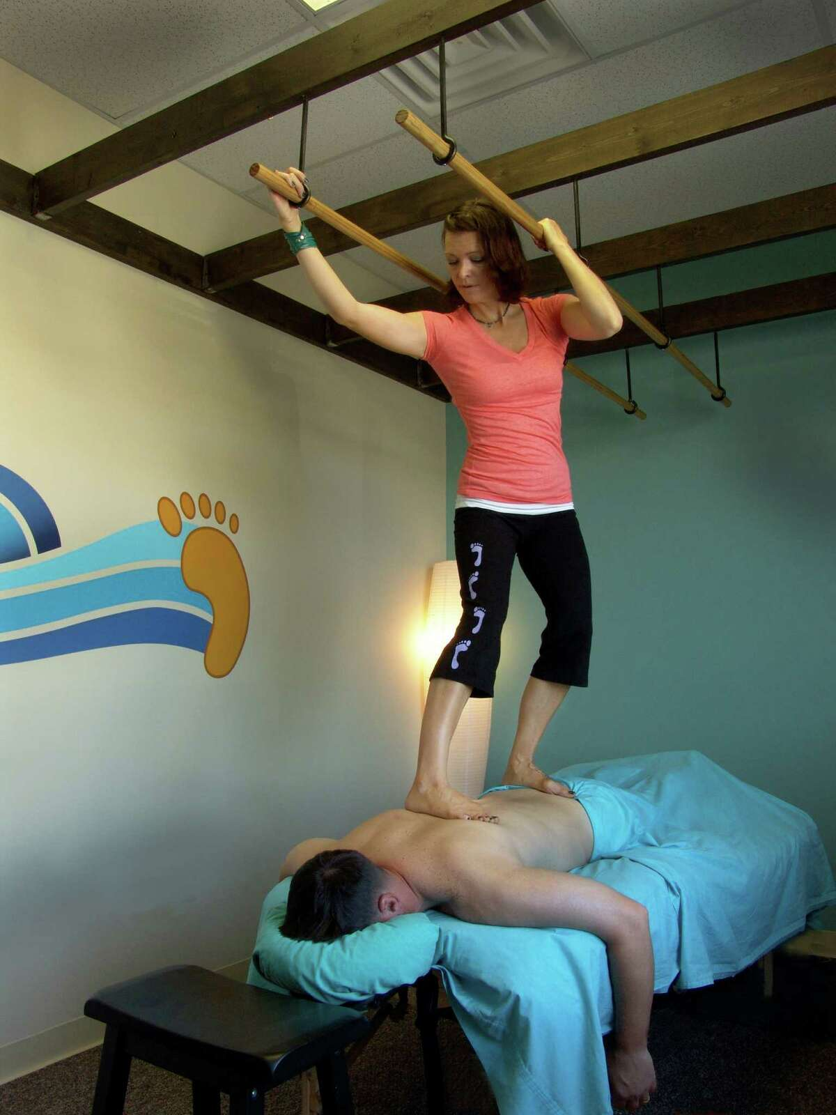 Jeni Spring of Heeling Sole gives an Ashiatsu massage, otherwise known as barefoot massage. Ashiatsu massage therapists use their feet instead of their hands to deliver massage by walking on their clients. Ashiatsu provides a deep-tissue massage, which can help alleviate chronic pain.
