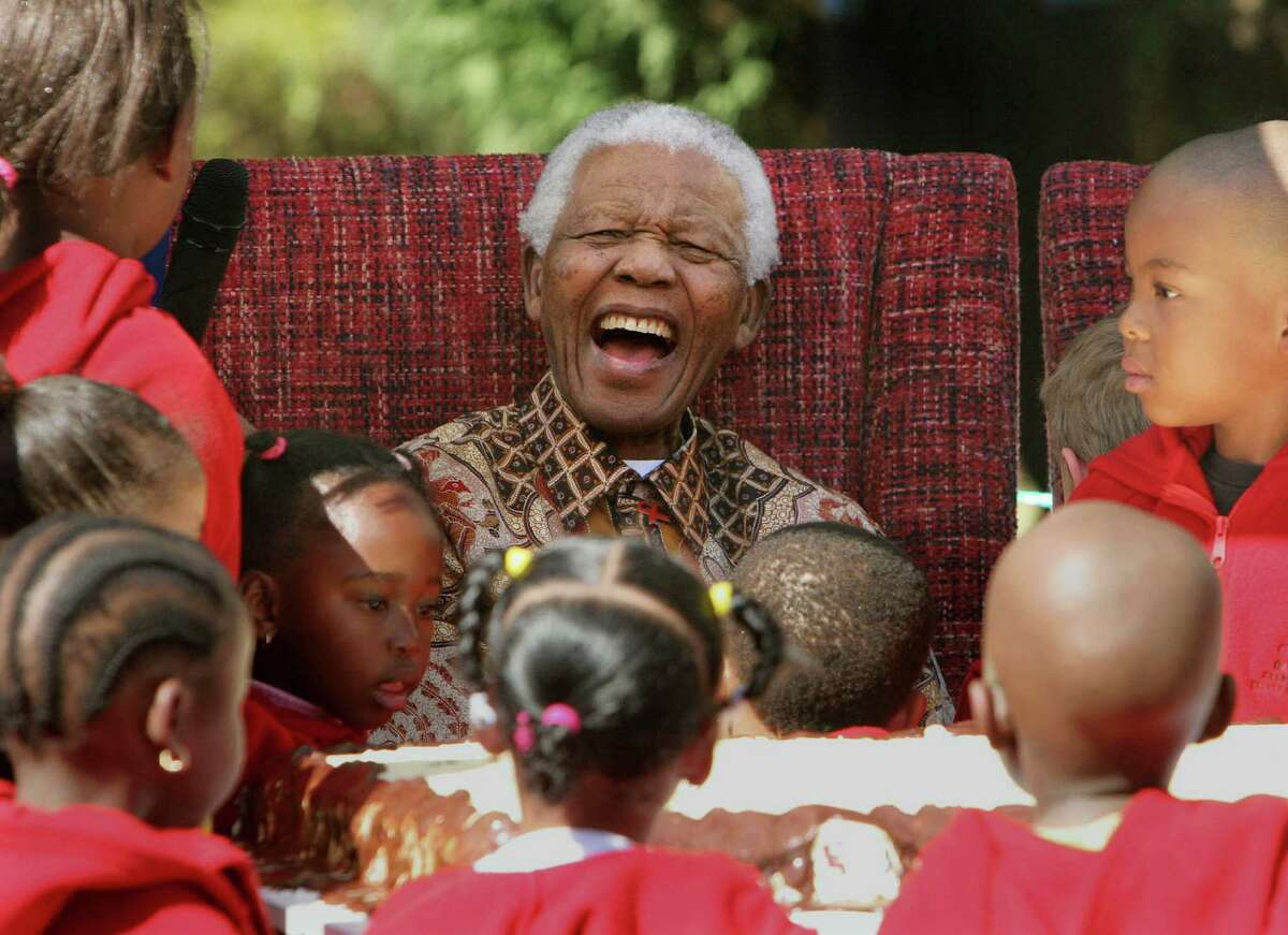 In this July 24, 2007 photo, former South African President Nelson Mandela laughs while celebrating his 89th birthday with children at the Nelson Mandela Children's Fund in Johannesburg. Thursday, Dec. 5, 2013, Mandela passed away. He was 95.