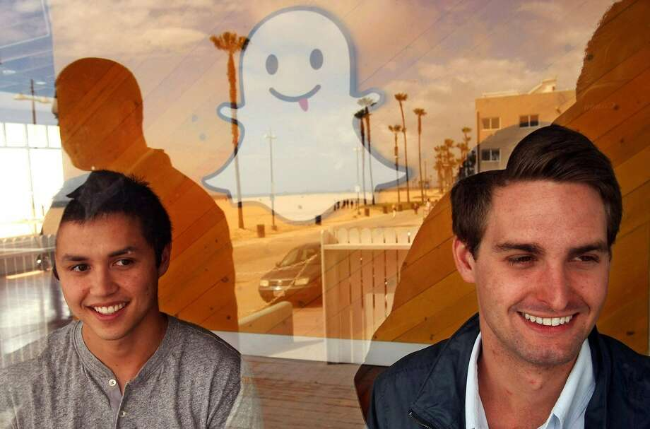 Snapchat co-creators Bobby Murphy, left, and Evan Spiegel are seen through a window at the company's offices in Venice, Calif., in May 2013. (Genaro Molina/Los Angeles Times/MCT) Photo: Genaro Molina, McClatchy-Tribune News Service
