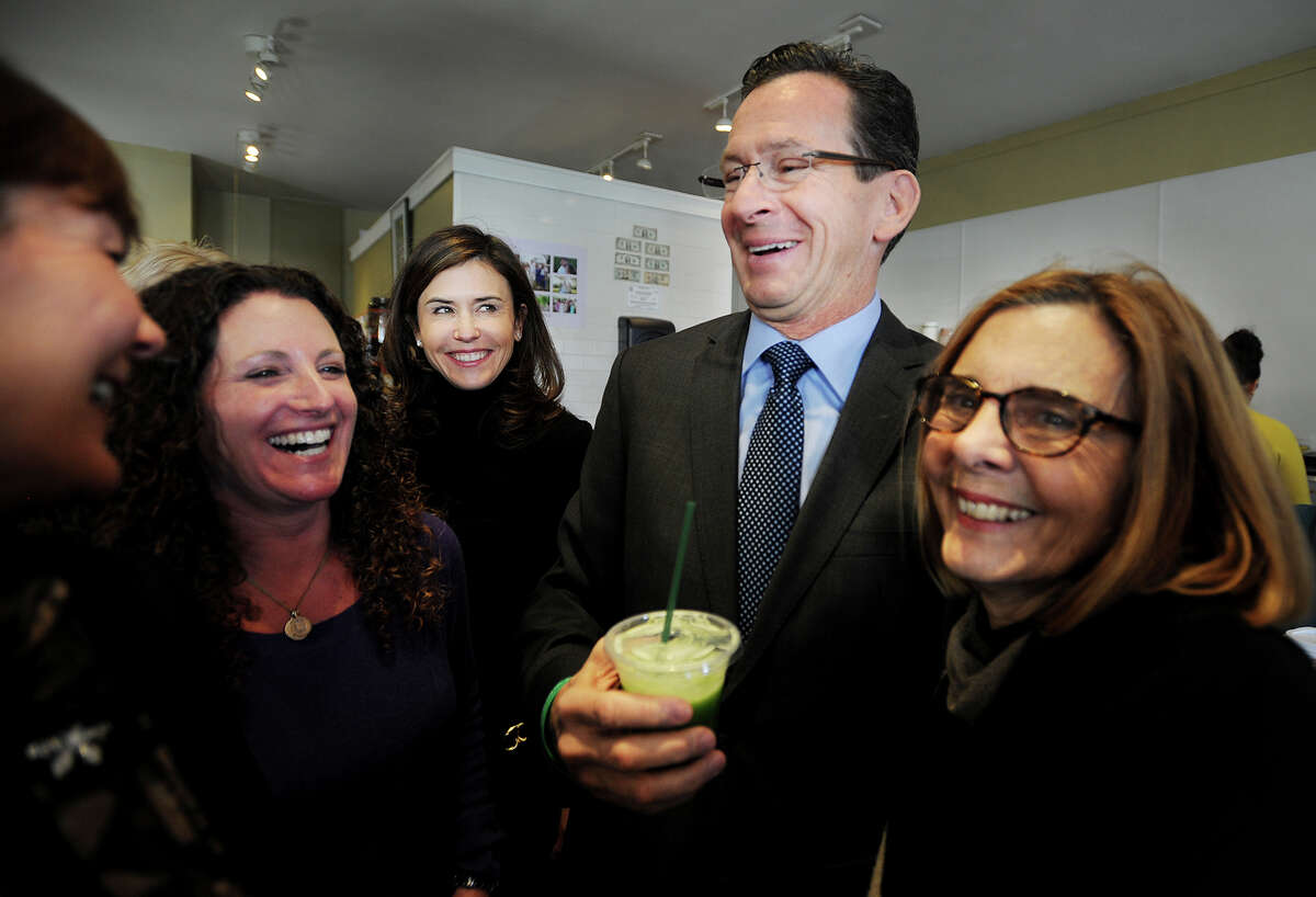 Governor Dannel P. Malloy samples a juice drink with Tara Cook-Littman, second from left, after a ceremonial bill signing of Public Act 13-183, that requires the labeling of genetically engineered foods, at Catch a Healthy Habit Cafe at 39 Unquowa Road in Fairfield, Conn. on Wednesday, December 12, 2013. Cook-Littman, of GMO Free CT, has been the driving force championing the GMO labeling law in the legislature.