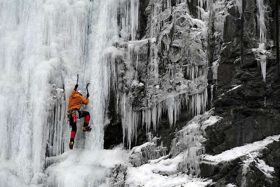 "Easy pickings: Andy Mamrol ascends an ice wall called the ""Roadside Attraction"" near mile 113 of the Seward Highway south of Anchorage, Alaska. Mamrol said the ""hero ice"" was soft enough to easily accommodate ice tools and crampons without shattering. Photo: Erik Hill, Associated Press"