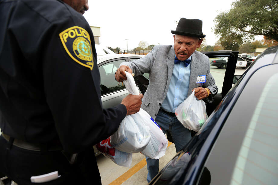 Tudy DuRiso hands bags of donated materials to BISD Police Chief Clydell Duncan on Wednesday. Stephen A. Mosely and DuRiso delivered donations to the Beaumont Independent School District Police Department on Wednesday afternoon. They and Unity Radio in Port Arthur had been gathering the donations for about four months. Photo taken Jake Daniels/@JakeD_in_SETX Photo: Jake Daniels / ©2013 The Beaumont Enterprise/Jake Daniels