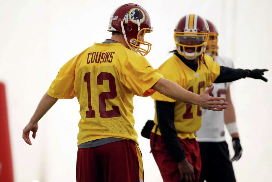 Washington Redskins quarterbacks Kirk Cousins, left, and Robert Griffin III, work during their NFL football practice Wednesday, Dec. 11, 2013, in Ashburn, Va. Kirk Cousins will start for the Washington Redskins on Sunday, and Robert Griffin III will be the No. 3 quarterback behind Rex Grossman. (AP Photo/Alex Brandon) Photo: Alex Brandon, Associated Press / AP