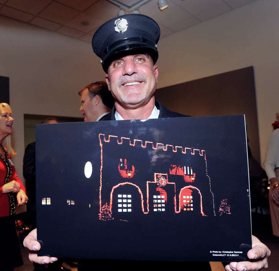 Jeff Franze, a Cos Cob volunteer firefighter, holds up a photo of the Cos Cob Firehouse that he helped decorate and that won the award for Best Classic Holiday Storefront in Cos Cob & Riverside, during the Greenwich Chamber of Commerce annual Holiday Storefront Decorations Awards Presentation at the Bruce Museum in Greenwich, Wednesday night, Dec. 11, 2013. Photo: Bob Luckey / Greenwich Time