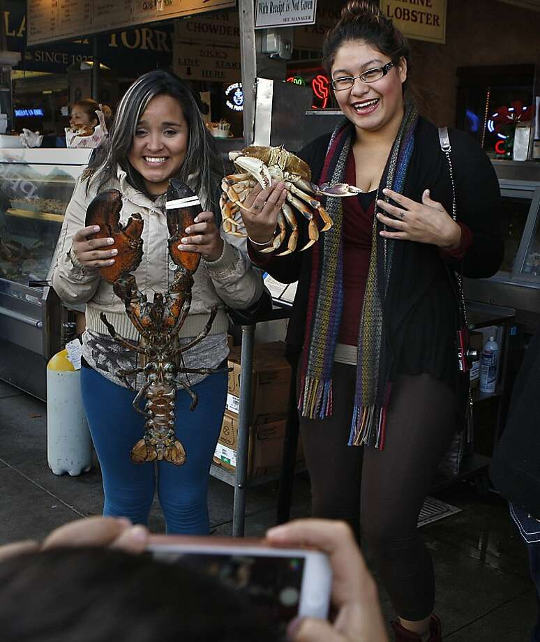 Tourists pose with a live lobster and crab at Nick's Lighthouse, which opened in the 1930s as the Lighthouse. The restaurant is wedged between Alioto's and Sabella & La Torre. Photo: Liz Hafalia, Chronicle