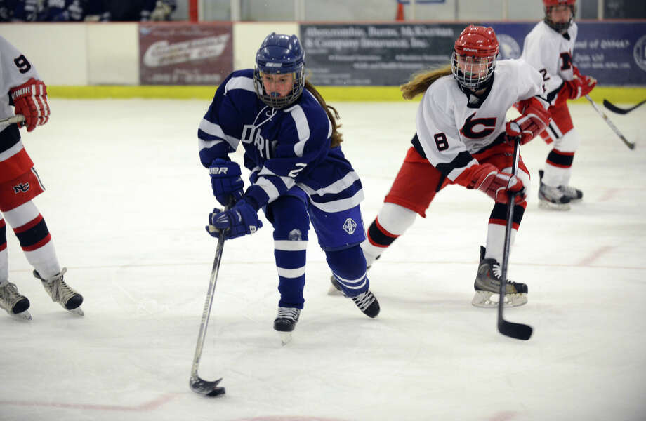 Darien's Georgia Cassidy (2) controls the puck as New Canaan's Emily Patch (8) defends during the girls ice hockey game at the Darien Ice Rink on Wednesday, Dec. 11, 2013. Photo: Amy Mortensen / Connecticut Post Freelance