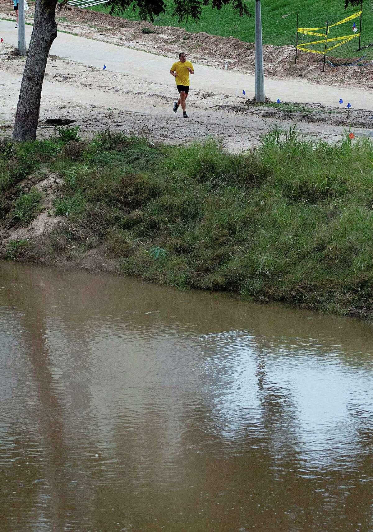 A runner jogs next to Buffalo Bayou as construction on Buffalo Bayou Park continues near downtown Monday, Nov. 4, 2013, in Houston. ( Johnny Hanson / Houston Chronicle )