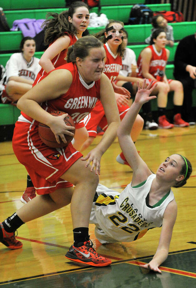 Greenwich's Emily Anderson dribbles around the diving Anne Peltier, of Trinity Catholic, during their game at Trinity Catholic High School in Stamford, Conn., on Wednesday, Dec. 11, 2013. Greenwich won, 68-32. Photo: Jason Rearick / Stamford Advocate