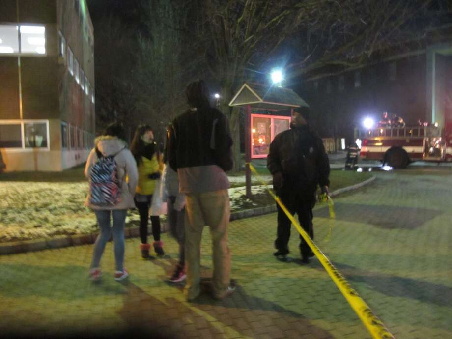 Students talk to a security guard monitoring the area around the John J. Cox Student Center, which caught fire Wednesday night. A large area around the center remained blocked for more than hour after the fire was out. Photo: Wes Duplantier, Connecticut Post