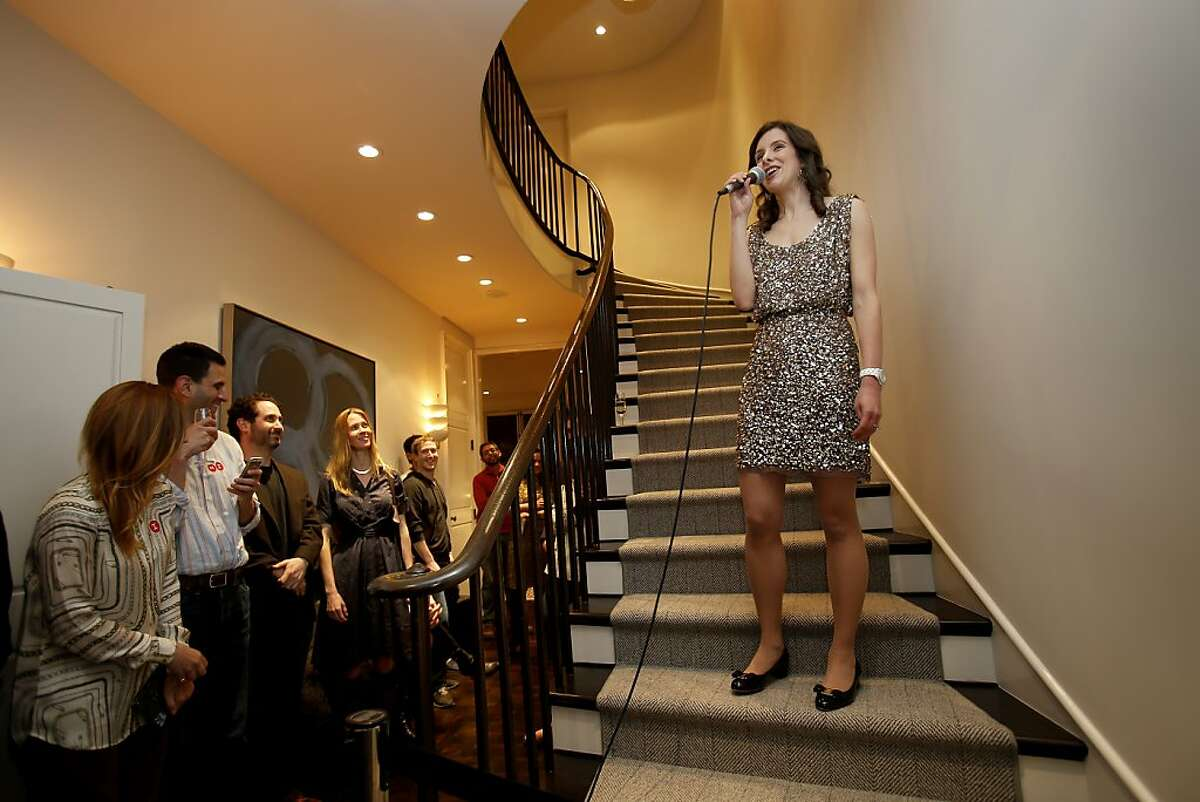 Facebook CEO Mark Zuckerberg stands in the background as Jessica Lessin talks about her new venture on the staircase Tuesday December 10, 2013 in San Francisco, Calif. Jessica Lessin, formerly with the Wall Street Journal, is starting a new premium tech news service called The Information. She had a launch party in Pacific Heights.