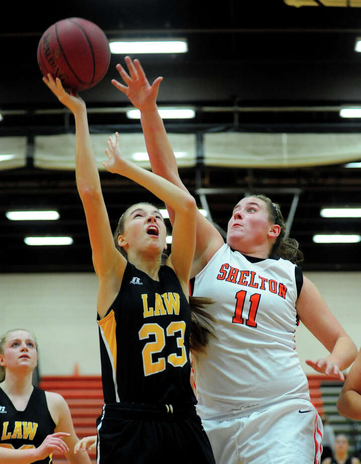 Shelton's Nicole Roberts, right, looks to block a shot by Jonathan Law's Lianne Maynard, during girls basketball action in Shelton Conn. on Wednesday December 11, 2013. Photo: Christian Abraham / Connecticut Post