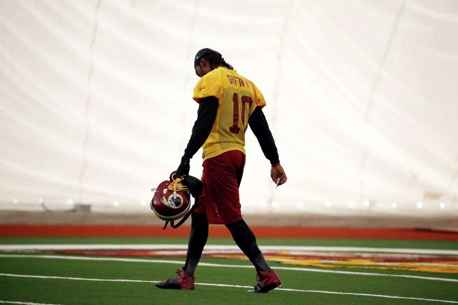 Washington Redskins quarterback Robert Griffin III, walks on the field during an NFL football practice Wednesday, Dec. 11, 2013, in Ashburn, Va. Quarterback Kirk Cousins will start for the Redskins on Sunday, and Griffin III will be the No. 3 quarterback behind Rex Grossman. (AP Photo/Alex Brandon) ORG XMIT: VAAB106 Photo: Alex Brandon / AP