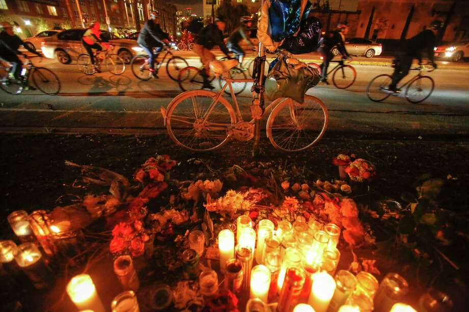 Cyclists ride near a memorial for Chelsea Norman to help promote better enforcement of laws when it comes to riding on public streets on Dec. 11, 2013, in Houston near Waugh and Dallas streets. The goal was to keep bike riders safer. Norman, who died on Dec. 4, was struck by a hit-and-run driver on Waugh. Photo: Eric Kayne, For The Chronicle / Eric Kayne