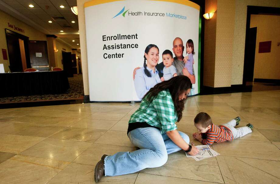 Karla Hay, left, colors with her son Anthony Hay, right, as they wait to speak a representative about health insurance under the Affordable Care Act at the Crowne Plaza in December 2013. Photo: Cody Duty, Houston Chronicle / © 2013 Houston Chronicle