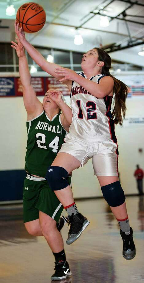 Norwalk high school's Mallory Rochefort tries to stop Brien McMahon high school's Kyle Courtney from getting a layup during a girls basketball game played at Brien McMahon high school, Norwalk, CT on Wednesday, December, 11th, 2013. Photo: Mark Conrad / Connecticut Post Freelance
