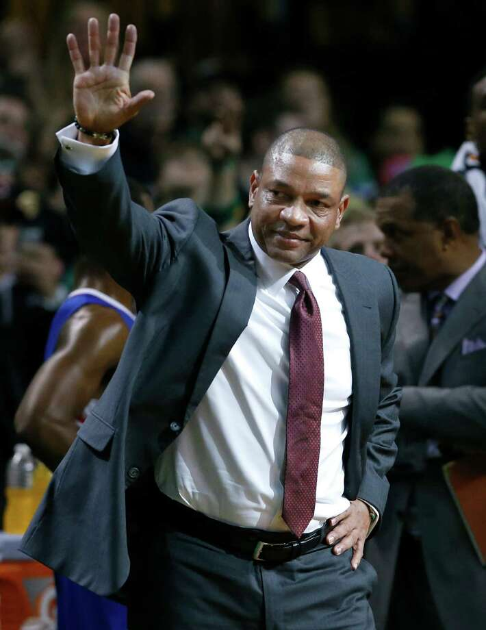 Current Los Angeles Clippers head coach and former Boston Celtics head coach Doc Rivers waves during a video tribute to him for his first time back to the TD Garden, after the first quarter of an NBA basketball game in Boston, Wednesday, Dec. 11, 2013. (AP Photo/Elise Amendola) ORG XMIT: MAEA103 Photo: Elise Amendola / AP