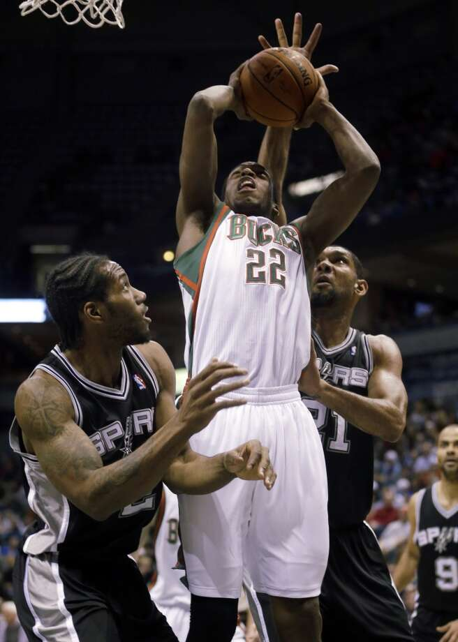 Milwaukee Bucks' Khris Middleton(22) has his shot blocked as he goes up against San Antonio Spurs' Tim Duncan (21) and Kawhi Leonard during the first half of an NBA basketball game Wednesday, Dec. 11, 2013, in Milwaukee. (AP Photo/Morry Gash) Photo: Associated Press