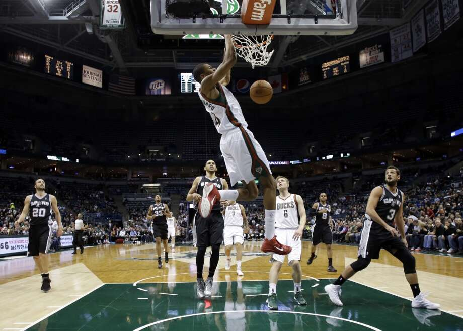Milwaukee Bucks' Giannis Antetokounmpo, front, dunks during the first half of an NBA basketball game against the San Antonio Spurs Wednesday, Dec. 11, 2013, in Milwaukee. (AP Photo/Morry Gash) Photo: Associated Press
