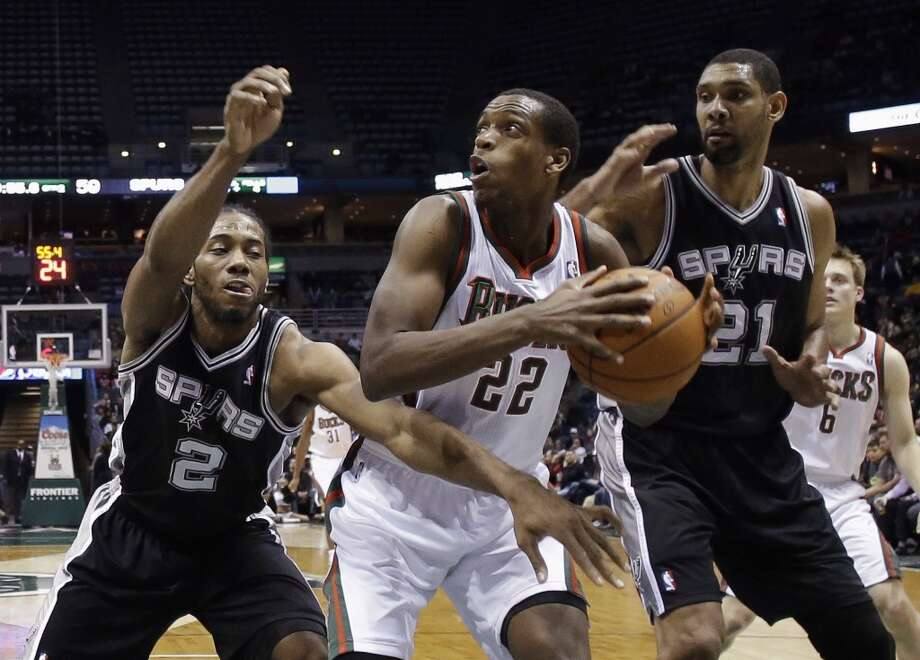 Milwaukee Bucks' Khris Middleton(22) tries to drive between San Antonio Spurs' Kawhi Leonard (2) and Tim Duncan (21) during the first half of an NBA basketball game Wednesday, Dec. 11, 2013, in Milwaukee. (AP Photo/Morry Gash) Photo: Associated Press